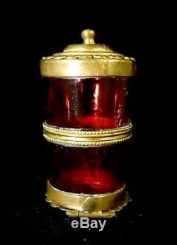 Petit flacon en laiton et verre rouge vue miniature fixé sous verre opaline